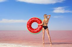 Beautiful woman with inflatable ring posing near pink royalty free stock photo