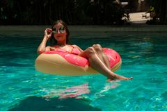 Beautiful woman and inflatable swim ring in shape of a donut in the pool. royalty free stock image