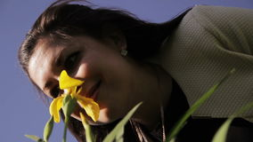 Beautiful woman inhales the scent of flowers stock footage