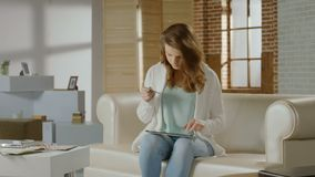 Beautiful woman inserting card number on tablet, online banking stock footage