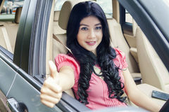 Beautiful woman inside car shows OK sign Royalty Free Stock Images