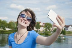 Beautiful woman, instagram. woman taking a selfie with smart phone outdoors in the city on sunny summer day. Closeup shot. royalty free stock images