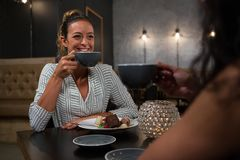 Beautiful woman interacting while having coffee. In restaurant Royalty Free Stock Photos