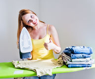 Beautiful woman ironing clothes in room on grey background Stock Photos