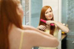 Beautiful Woman Ironing Healthy Red Hair With Iron Straightener. Beautiful redhead girl using electric hair straightener in bathroom. Pretty woman ironing hair Stock Photo