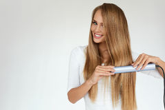 Beautiful Woman Ironing Long Straight Hair With Straightener. Hairstyle. Beautiful Smiling Woman Ironing Long Blonde Hair With Flat Iron. Portrait Of Girl With Royalty Free Stock Image