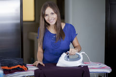 Beautiful woman ironing some clothes Royalty Free Stock Photo