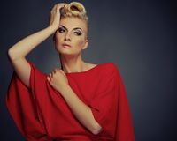 Beautiful woman isolated on grey. Fashionable woman in red with creative hairstyle Stock Photography