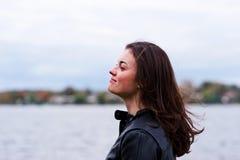 Beautiful woman in a jacket. Beautiful woman enjoying the breeze from the water Stock Image