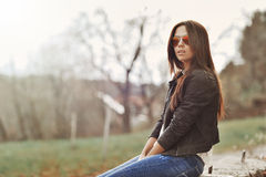 Beautiful woman in jacket and jeans sitting in a park Royalty Free Stock Photos