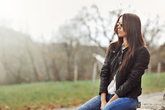 Beautiful woman in jacket and jeans sitting in a park Stock Photo
