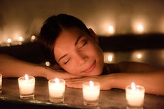Beautiful Woman In Jacuzzi With Lit Candles At Spa. Beautiful young woman relaxing in jacuzzi hot tub at spa. Attractive female tourist is surrounded with lit Stock Photos