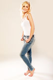 Beautiful woman in jeans posing barefoot Royalty Free Stock Photo