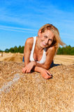 Beautiful woman in jeans short  posing on a wheat bale in a field Stock Photo
