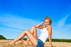 Beautiful woman in jeans short  posing on a wheat bale in a field Royalty Free Stock Photos