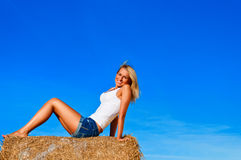 Beautiful woman in jeans short  posing on a wheat bale in a field Royalty Free Stock Image