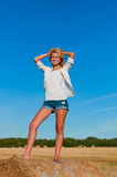 Beautiful woman in jeans short and white shirt posing Royalty Free Stock Image