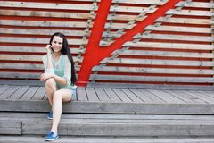Beautiful woman in jeans shorts sitting on wooden steps. Stock Photos
