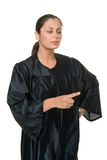 Beautiful Woman Judge Pointing. Beautiful Hispanic woman judge in black judicial robes standing and gesturing by pointing with her index finger Royalty Free Stock Image