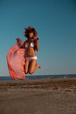 Beautiful woman jumping for joy desert beach Royalty Free Stock Photos