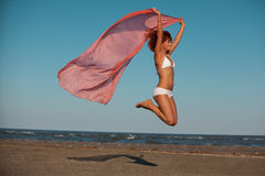 Beautiful woman jumping for joy desert beach Royalty Free Stock Images