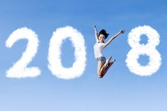Beautiful woman jumping with numbers 2018. Beautiful woman jumping with clouds shaped numbers 2018 in the blue sky Royalty Free Stock Photography