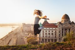 Beautiful woman jumping opposite famous facade and entrance to Hotel Gellert on banks of Danube in Budapest, Hungary royalty free stock photo