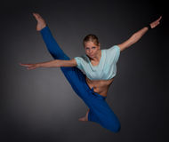 Beautiful woman jumping in the splits. Young beautiful blonde woman jumping in the splits Royalty Free Stock Photography