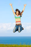 Beautiful woman jumping up in the air smiling Stock Photography