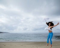 Beautiful woman jumping with a white umbrella at beach Stock Image