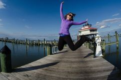 Beautiful woman jumps on a dock alongside the Choptank River Lighthouse in Maryland. Fisheye view stock images