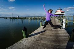Beautiful woman jumps on a dock alongside the Choptank River Lighthouse in Maryland. Sunny day, photo taken in fisheye lens royalty free stock photo