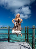 Beautiful woman jumps up on a wooden platform over the sea Royalty Free Stock Photos