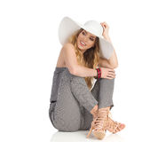 Beautiful Woman In Jumpsuit, Sun Hat And High Heels Is Sitting on Floor And Looking Away Stock Image