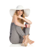 Beautiful Woman In Jumpsuit, Sun Hat And High Heels Is Sitting on Floor Royalty Free Stock Image