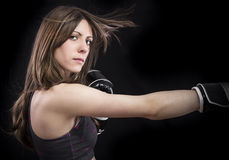 Boxer woman during boxing exercise making direct hit with black Royalty Free Stock Photography