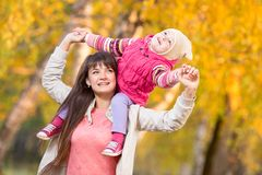 Beautiful woman with kid girl outdoor in autumnal royalty free stock image