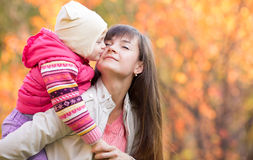 Beautiful woman with kid girl outdoor fall. Child kissing mo Royalty Free Stock Image