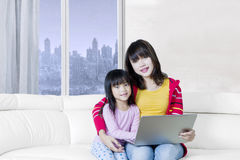 Beautiful woman and kid with laptop on sofa Royalty Free Stock Photography