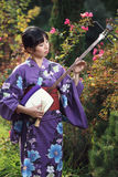 Beautiful woman with kimono playing shamisen Royalty Free Stock Photo