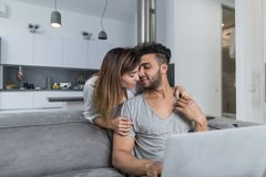 Beautiful Woman Kiss Man Sitting On Couch With Laptop Computer In Modern Apartment Young Couple Spend Time Together At Royalty Free Stock Photography