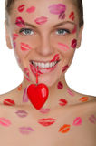 Beautiful woman with kisses on face holding heart in teeth Royalty Free Stock Photos