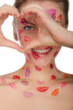 Beautiful woman with kisses on her face shows heart Royalty Free Stock Image