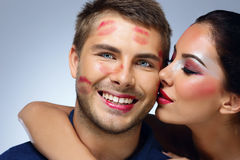 Beautiful woman kissing happy man Stock Images