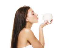 Beautiful woman kissing a piggy bank Stock Images