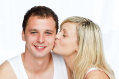 Beautiful woman kissing a smiling man Royalty Free Stock Image