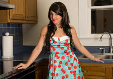 Beautiful Woman in Kitchen. A fun image with a retro feel of a pretty young woman in a dress and pearls in a kitchen Stock Photography