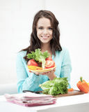 Beautiful woman in the kitchen cutting vegetables Royalty Free Stock Image