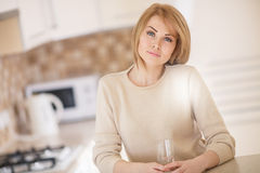Beautiful woman in the kitchen with a glass of water Stock Images