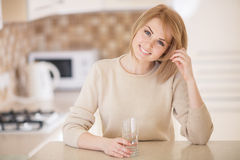 Beautiful woman in the kitchen with a glass of water Royalty Free Stock Images